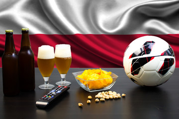 2 bottles of beer, 2 glasses of beer next to the football on the background of the flag of Poland.