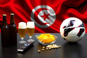 2 bottles of beer, 2 glasses of beer next to the football on the background of the flag of Tunisia.