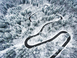 Foto auf AluDibond Grau Snowy road in the forest. Extreme winding road high up in the mountains