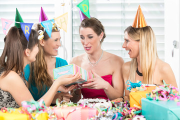 Cheerful woman holding a gift box while looking up overwhelmed by the appreciation of her best friends during a surprise birthday party at home