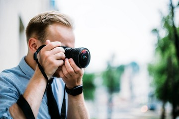 young man photographer shoots a mirrorless camera and fisheye lens. A tourist with a camera in the city and nature.