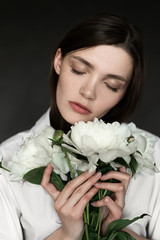 Portrait of a beautiful girl with peonies. Beauty retouching photo. Fashion and cosmetic concept. Grey studio background.