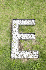 Letter E built from white stones on green grass as seen from high above
