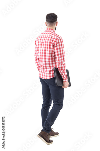 d5b50bd9464b Rear view of young adult business man carrying laptop under arm walking and  looking away. Full body isolated on white background.