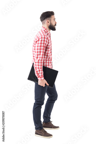 a8058e9ba604 Side view of modern stylish bearded millennial business man walking and  carrying laptop under arm. Full body isolated on white background.