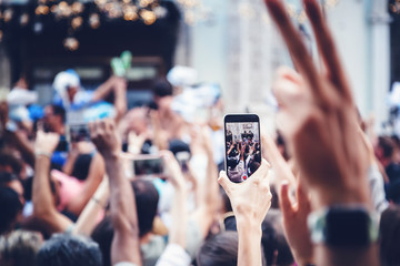 Smartphone in female hand, hand with phone over crowd - shooting event concept, live broadcast, instant, speed of information