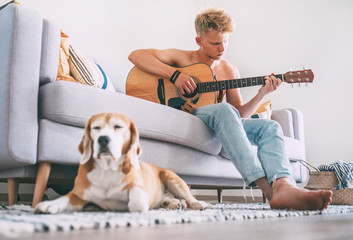 Young man plays on guitar sitting on the sofa at home and beagle dog dreams near on the floor