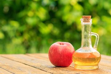 Apple vinegar in glass bottle and fresh red apple on wooden boards