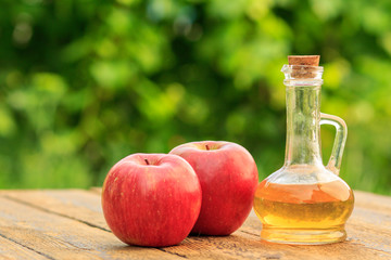 Apple vinegar in glass bottle and fresh red apples on wooden boards