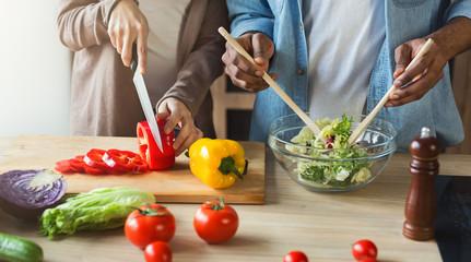 Black couple preparing vegetable salad together
