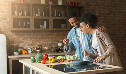 Happy african-american couple preparing dinner