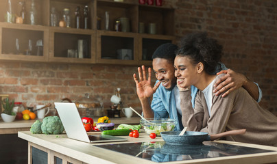 Black couple using laptop and greeting in kitchen