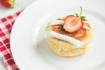 Homemade cottage cheese pancakes with sour cream and fresh strawberry on white wooden background. Healthy breakfast.