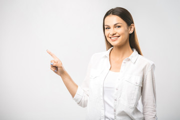 Young beautiful woman presenting your product, isolated over white background. Place for text. Female hand pushing a digital screen at office background. Focus on finger.