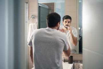 Hispanic Man Brushing Teeth In Bathroom At Morning