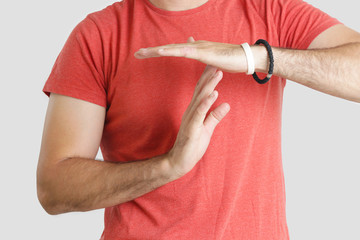 Young man in a red t shirt showing time out sign with his hands, studio shot, isolated