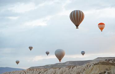 Hot air balloons flying over the rocks of Cappadocia