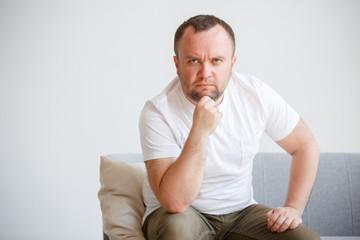 Image of man in white T-shirt sitting on sofa