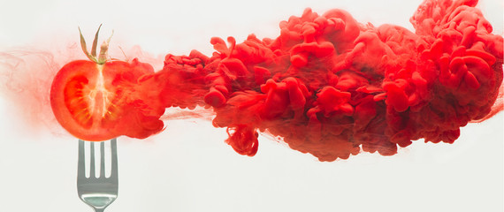Fresh tomato on a fork with a cloud of dissolving color. Artistic nutrition concept. Science of food action photography