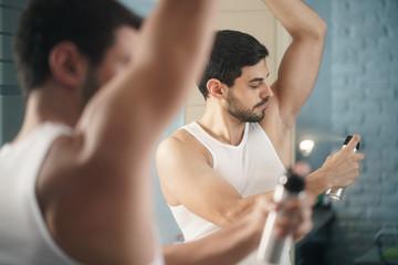 Man Using Spray Deodorant On Underarm For Bad Smell