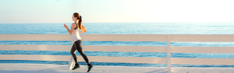 Slim girl in sportswear running on white wooden promenade by the sea.