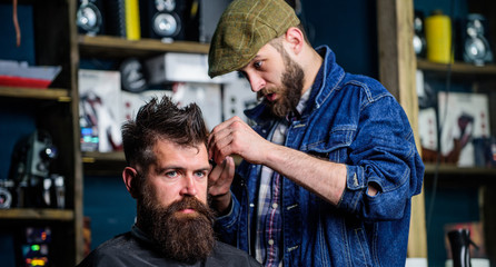 Barber in denim jacket busy with trimming hipster, barbershop background. Client with beard and mustache covered with cape. Image making concept. Barber work on haircut with hair clipper equipment