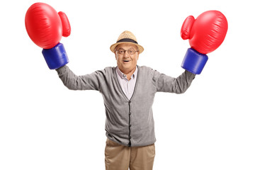 Mature man wearing a pair of big boxing gloves flexing his biceps