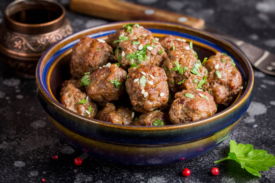 Beef meatballs in bowl with sauce, brown with sesame and parsley, tatsy snack