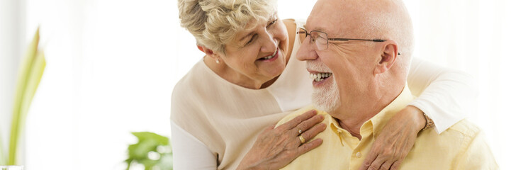 Portrait of a happy, laughing senior couple - an elderly woman standing behind her husband with arms around him