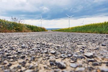 Weitwinkel Aufnahme eines Feldweges, an den Seiten liegen Getreidefelder mit Blick auf Wind Generatoren vor bewölktem Himmel