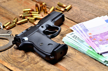 9mm pistol - handgun, handcuffs, bullets and euro banknotes on old wooden table
