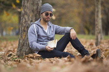 Handsome man in nature reading a book. Autumn leaves. Copy space