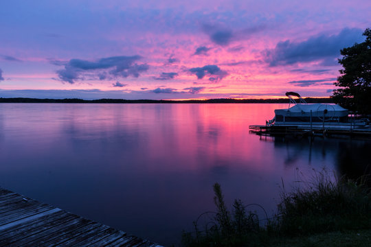 Colorful pink, purple & blue sunset over a calm lake with a pontoon boat at the shore. Beautiful northwoods scene with a colorful sky reflected in the water. Concepts of vacation, nature, travel