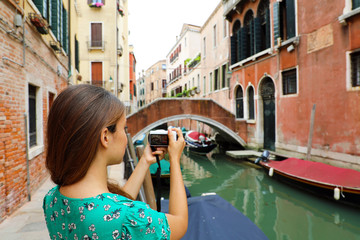 Young woman taking picture with mirrorless camera of traditional canals sight of Venice, Italy