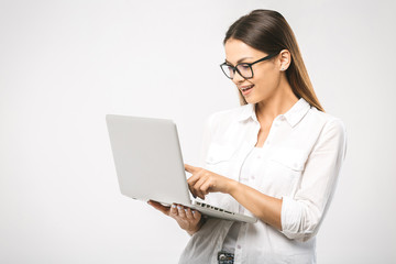 Portrait of happy surprised woman standing with laptop isolated on white background