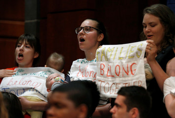 Protesters with children demonstrate against the Trump administration's practice of separating children from their parents before a joint hearing of the House Judiciary  and House Oversight and Government Reform Committee in Washington