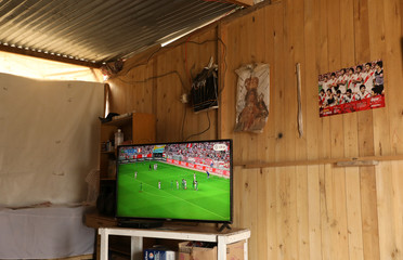 A TV shows a friendly soccer match between Peru and Saudi Arabia at the Mendez family home at Nueva Union shantytown in Villa Maria del Triunfo district of Lima