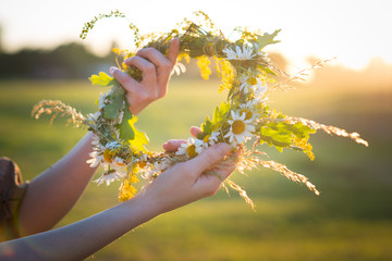 Midsummer in Latvia: celebration of Ligo - a young woman weave a wreath and collect field flowers