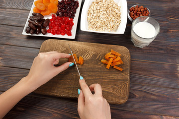 the girl is preparing her breakfast. Cutting dried fruits into oatmeal porridge on a cutting board. Useful and healthy breakfast. dark wooden background, top view