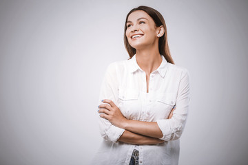 Portrait of happy smiling young beautiful woman, isolated over white background. Looking up. Free space for text.