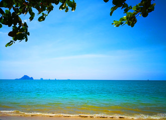 The beach of Southern Thailand. Small wave hit the shore. The sea is turquoise and the sky is clear, so you can see the small islands off the coast.