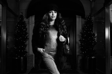 Gorgeous young woman with long brunette hair dressed in gray jumper, trousers and luxurious fur coat, holding handbag, posing on red carpet against building entrance and potted trees on background.