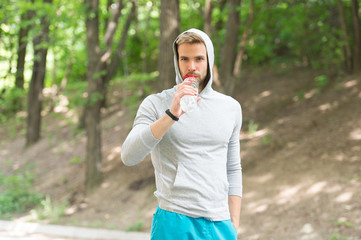 Sport and healthy lifestyle concept. Man with athletic appearance holds bottle with water. Man athlete in sport clothes training outdoor. Athlete drinks water after training, nature background
