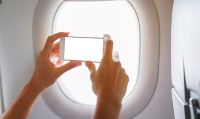 close up man hand holding smartphone (with blank screen) and take view photo at window seat in airplane for holiday concept