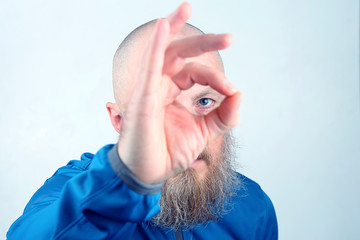portrait of a man with a beard looking through his fingers