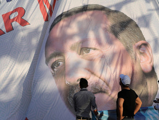 Men look at a large election poster of President Tayyip Erdogan in Mardin