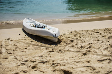 White kayak and paddle by the seashore on the beautiful white sand of Labadee, Haiti.  No people, quiet peaceful sunny day, endless views of the turquoise ocean.