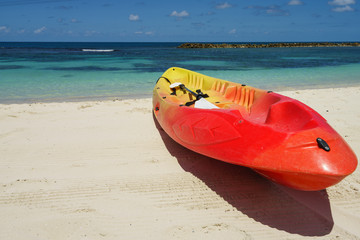 Yellow and red kayak and paddle by the seashore on the beautiful white sand of Labadee, Haiti.  No people, quiet peaceful sunny day, endless views of the turquoise ocean.