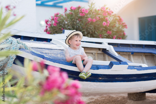 4f10a26cb Happy smiling child boy in straw hat sitting on boat at summer ...