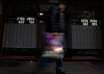 A man walks by an electronic board showing currency exchange rates in Buenos Aires' financial district